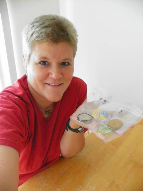 "Heather, aka ""Craftea"", with her recovered Geocoins still in the police evidence bag"