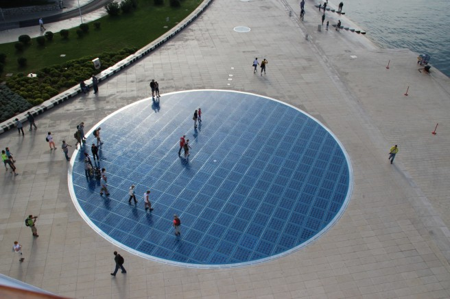 A series of solar panels arranged in a circle light up at night.