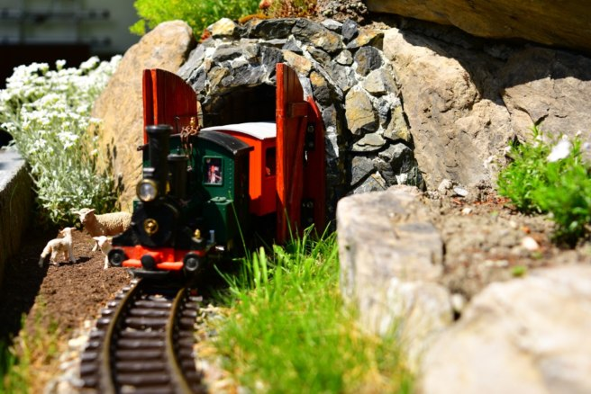 The train emerges from a gated tunnel with caboose in tow