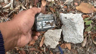 Hand placing a geocache container next to two rocks