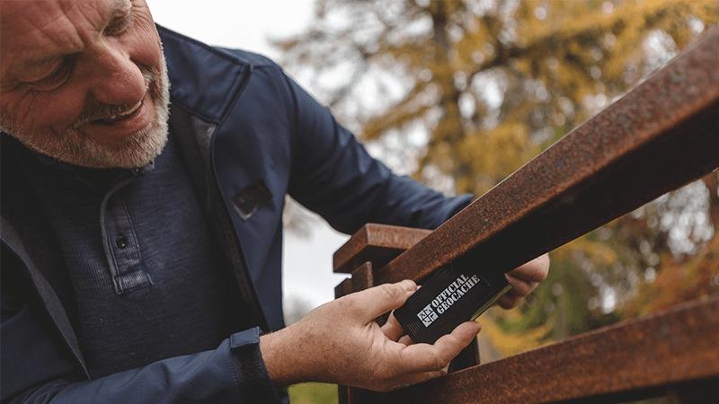 A geocacher finds a micro cache hidden under an outdoor handrailing