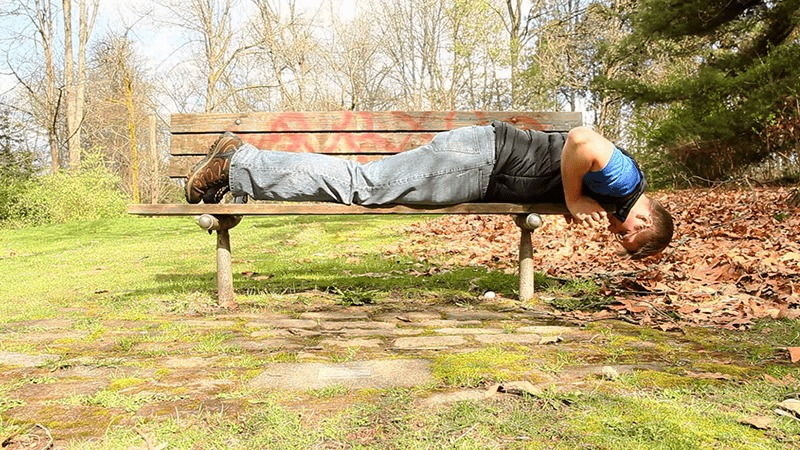 A geocacher lies across a park bench and reaches underneath it to try and find a geocache.